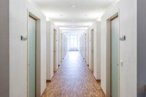 Long apartment hallway with doors along the sides