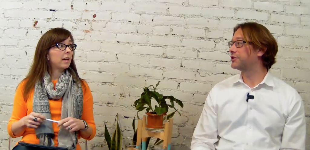CEO Felicite Moorman and CTO Ryan Buchert sitting next to each other looking at each other in front of a white brick background