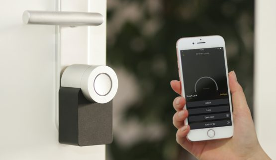Hand holding up a phone to a door with a smart lock