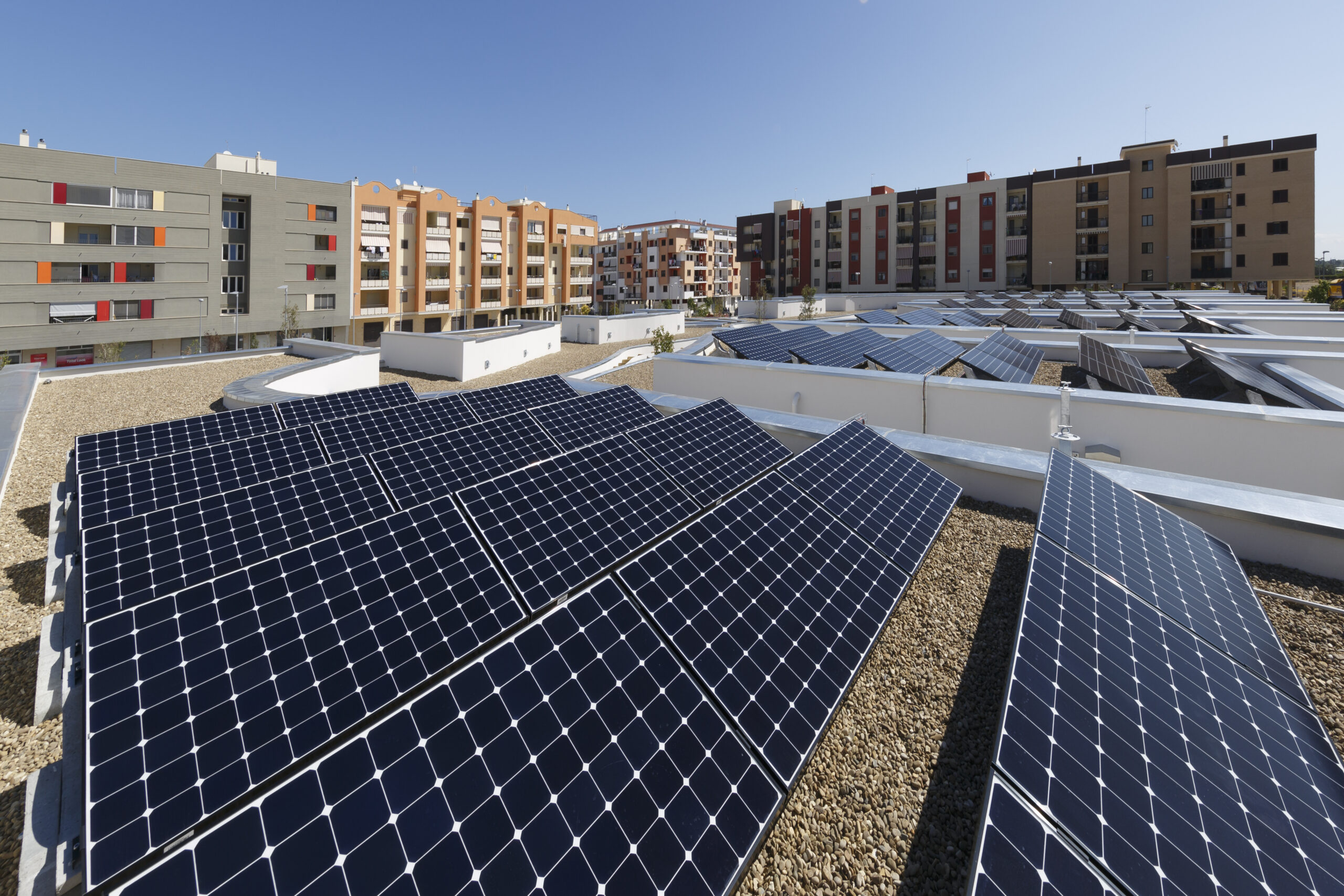 Solar panels installed on the apartment roof with surrounding apartments