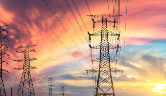 Several electricity transmission towers in front of a sunset
