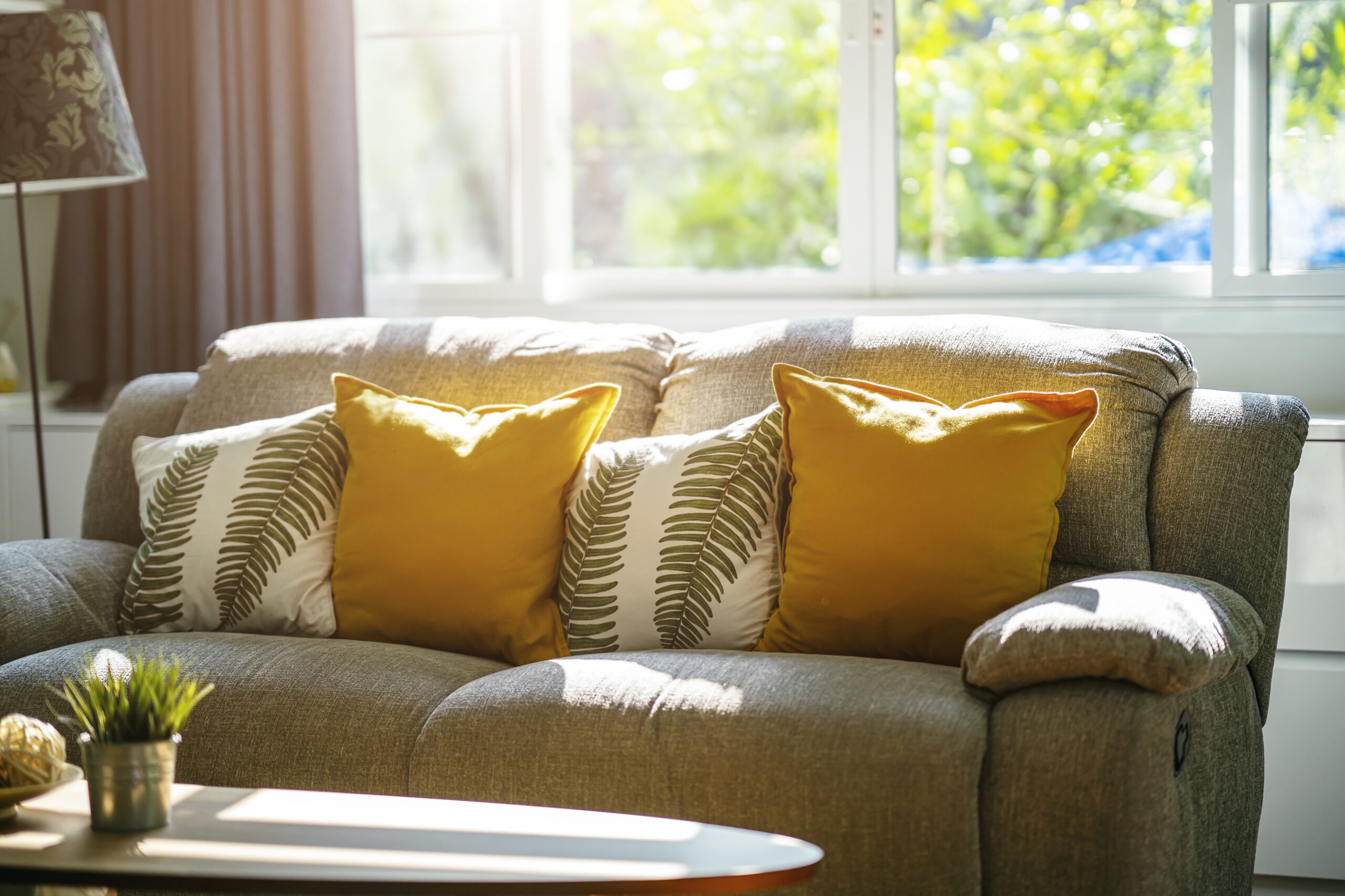 Couch in a room with sunlight from the window next to it illuminating the room