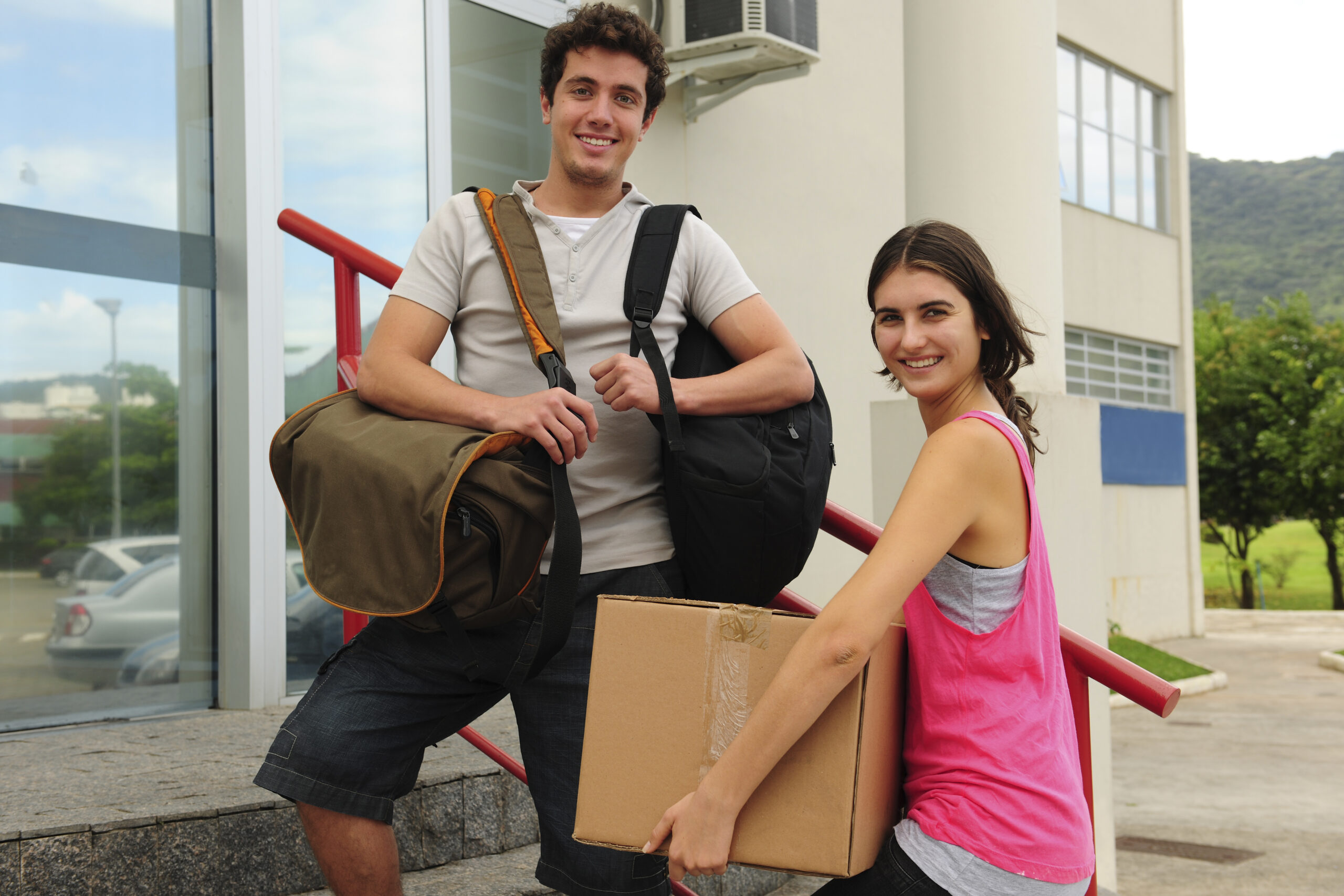 Two students carrying boxes and bags walking up the stairs of a building to move in