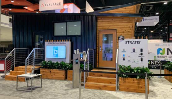 Small portable wooden house (the STRATIS Smart Suite) with the smart devices installed within it displayed outside it on a board at Apartmentalize